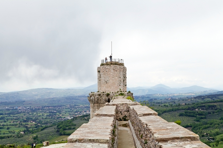Tourists are visiting the Rocca Maggiore, Assisi, Italy, with panorama. Rocca Maggiore dominated by more than eight hundred years the citadel of Assisi and the valley of Tescio. The first documented regarding the fortress date back to 1173.
