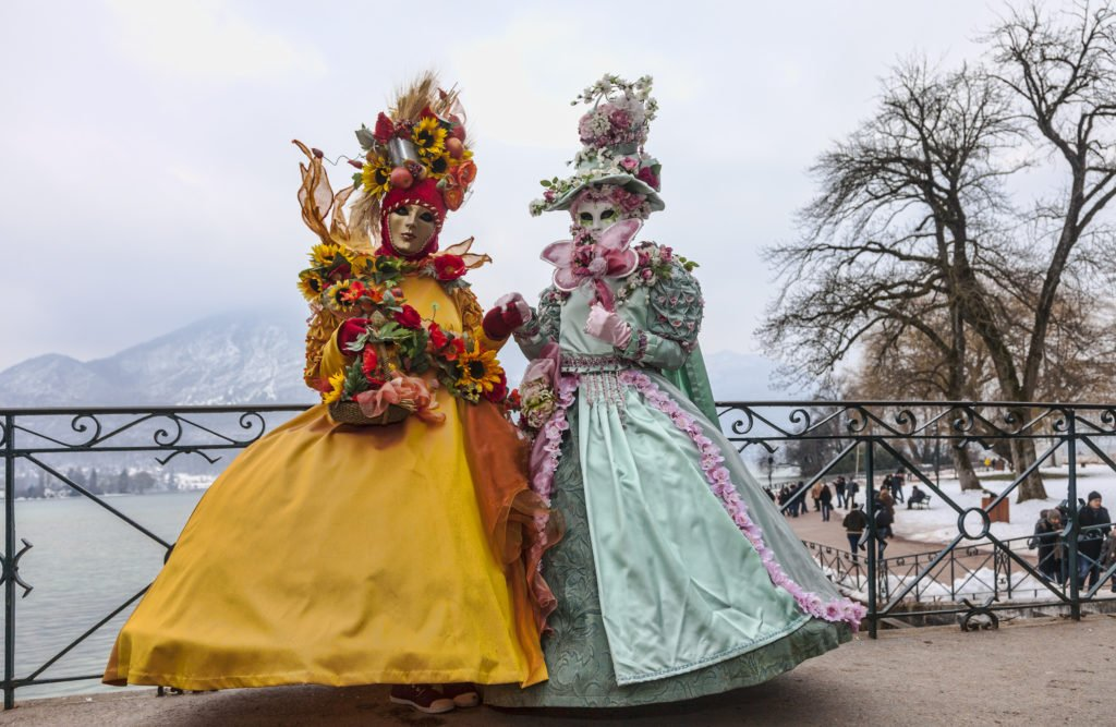 mardi gras festival france | Annecy, France, February 23, 2013: Couple disguised in beautiful costumes posing on the Lovers Bridge over a canal canal in Annecy, France, during a Venetian Carnival.