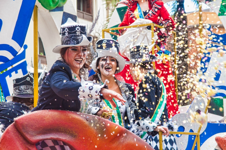 things to do in andalusia | ALGECIRAS, SPAIN - MARCH 05, 2017: Cheerful laughing Carnival participants throw confetti during the parade of the carnival in the street in Algeciras, Cadiz, Andalusia
