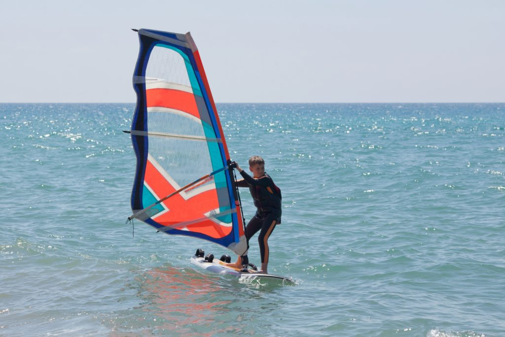 Windsurfing in a calm day with clear blue sky and Mediterranean Sea | family holiday in Mallorca