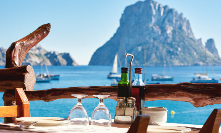 Outdoors restaurant at Cala d'Hort beach, with a fantastic view of the mysterious island of Es Vedra. Ibiza Island, Balearic Islands. Spain