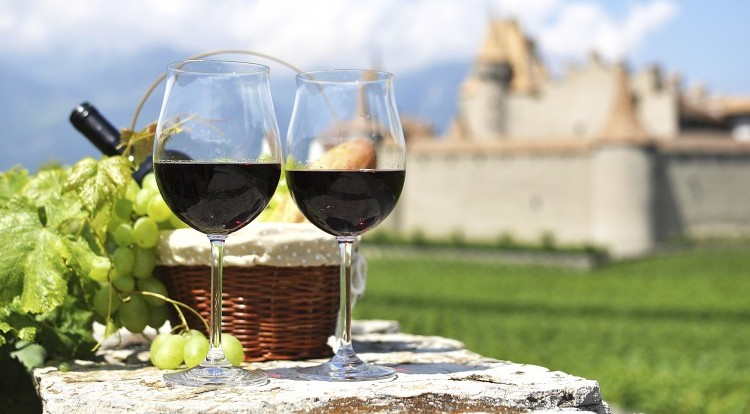 Red wine and grapes against an old castle. Switzerland
