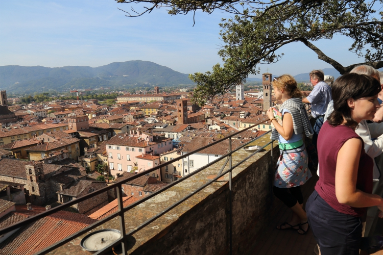best group activities in Tuscany | Lucca, Italy - September 28, 2017: Tourists admire the view from the Torre Guinigi tower in Tuscany in Lucca, Italy on September 28, 2017