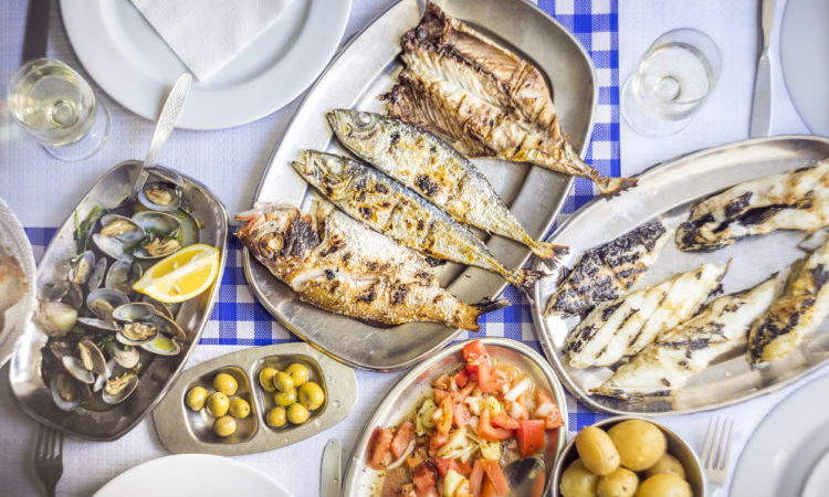 Fish feast: sea bass, golden, horse mackerel accompanied with tomato salad, clams, bread and white wine, Portugal