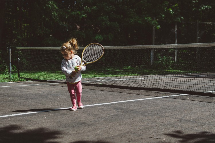 little girl holding tennis racket on tennis court