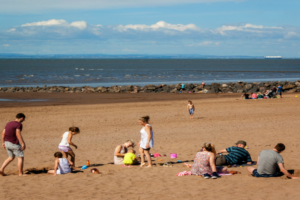 People walking and enjoying a summer day in a shoreside in Minehead, UK