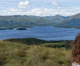 woman sitting overlooking a loch in Scotland