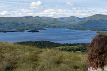 woman sitting overlooking a loch in Scotland