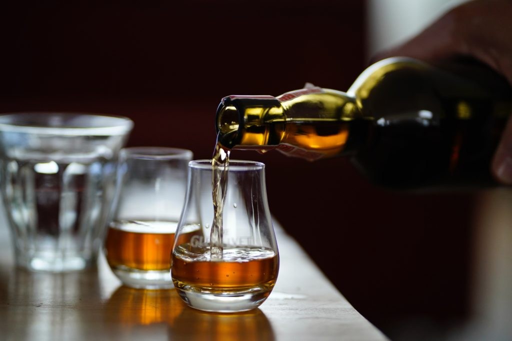 whisky being poured into two glasses