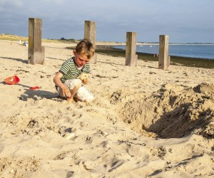 small boy playing on a sandy beach