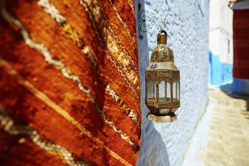 Carpet for sale and beautiful lantern on a street in Chefchaouen, Morocco, small town in northwest Morocco known for its blue buildings