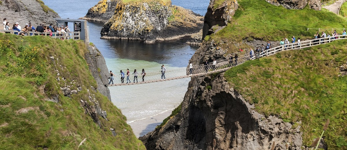 Tourist on the Carrick-a-Rede rope bridge on the Causeway Coast in Antrim County, Northern Ireland