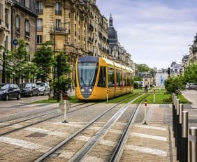 Reims, France, EU - June 27, 2012: Yellow city tram on the streets of Reims started in 2011 and is seen here on Cours Jean Baptiste Langlet in in this French city.