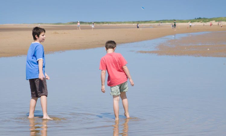 two boys paddling and talking in low tide, Norfolk, UK