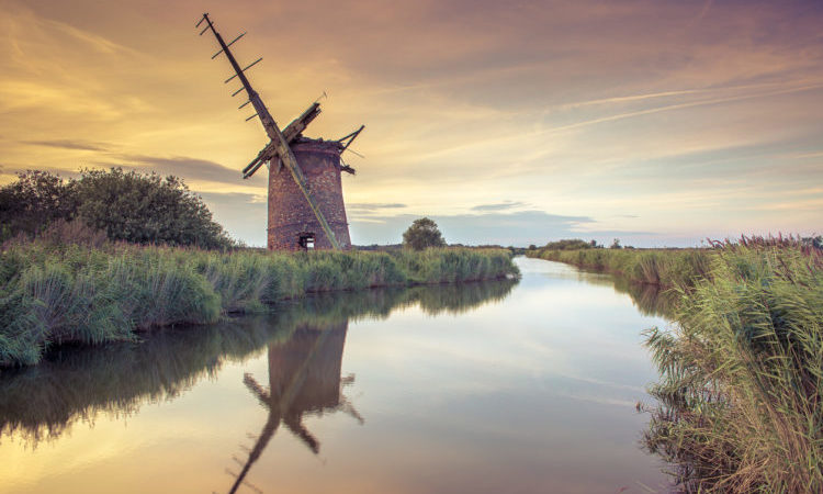 Abandoned Windmill on norfolk broads at sunset