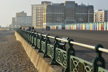Seafront promenade on misty winters day at Brighton, East Sussex, England. With people strolling around.
