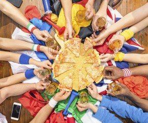 Top view of multiethnic hands of football sport supporter sharing pizza margherita - Friendship concept with soccer fans enjoying food together - People eating at party bar pub after sport match event
