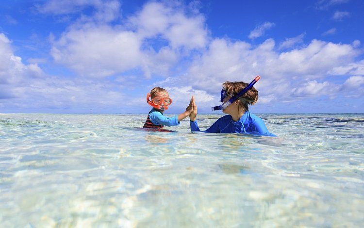 happy mother and son snorkeling on tropical beach