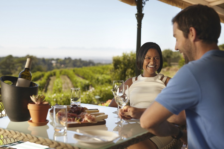 Happy young couple at winery restaurant with vineyard in background. Smiling young woman with a man sitting at table drinking wine.