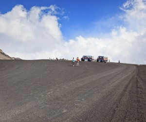 """""""Mt. Etna, Italy - August, 24 2010: A tour group of tourists exploring and taking photos of a high region of Mt Etna. Ascending Mt. Etna by a 4 x4 wheel drive vehicle is a unique experience giving tourists the opportunity to get reach cloud level."""""""
