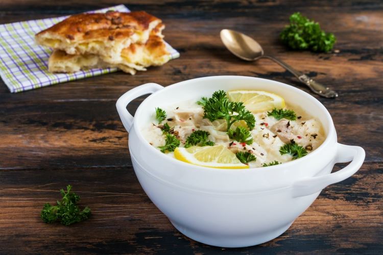 Avgolemono, chicken soup with egg-lemon sauce, rice and fresh parsley leaves in white bowl and freshly baked bread on wooden table.