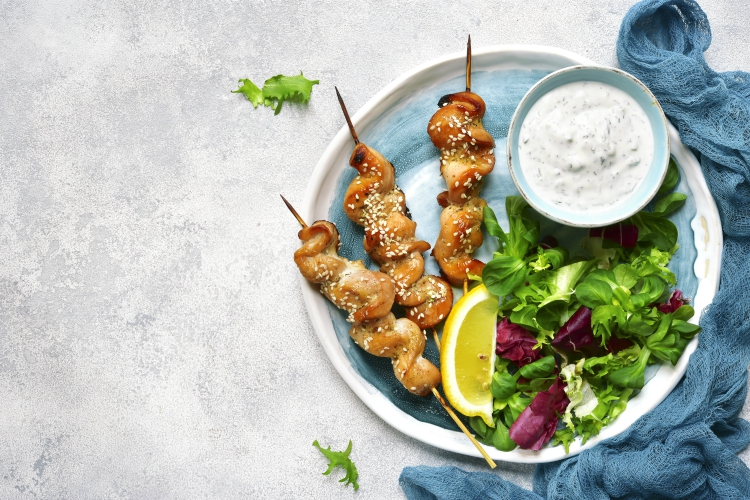 Grilled chiken breast on a skewers with mix of salad leaves on a plate on light slate,stone or concrete background.Top view.