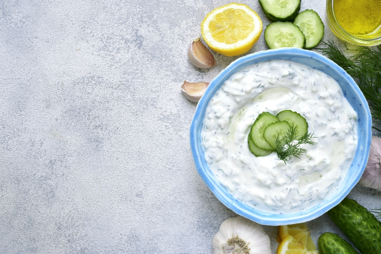 Tzatziki - yoghurt sauce with cucumber and dill on a light slate or stone background,traditional greek cuisine.Top view with copy space.