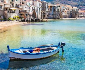 Beautiful old harbor with wooden fishing boat in Cefalu, Sicily, Italy.