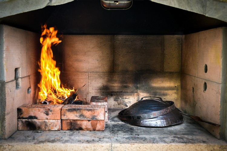 Cooking of traditional Balkan Greek Mediterranean Croatian meal Peka in metal pots called sac sach or sache or a metal lid. Fireplace with open fire and burning coals.