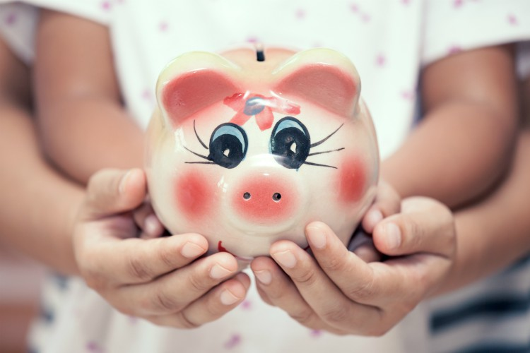 Piggy bank in child kid and mother hands in vintage color tone. family, saving, investments concept