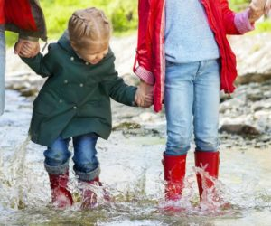 Happy family with two children wearing rain boots jumping into a mountain river