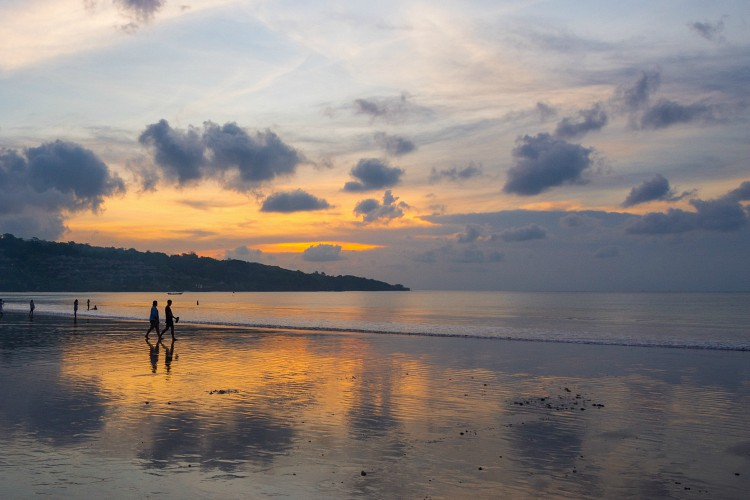 Holidaymakers enjoying a tropical sunset on Jimbaran Beach, one of the most popular beaches in Bali, Indonesia.