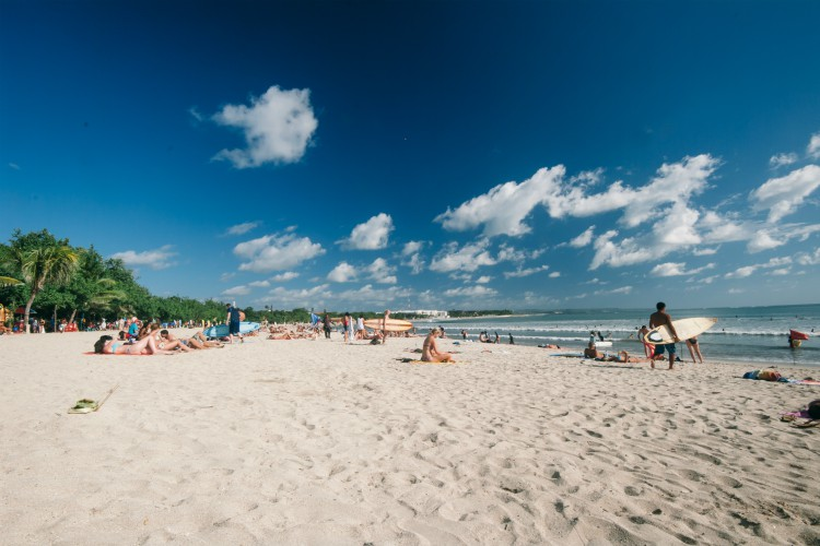tourist relax and enjoy surf in in the beach of Kuta