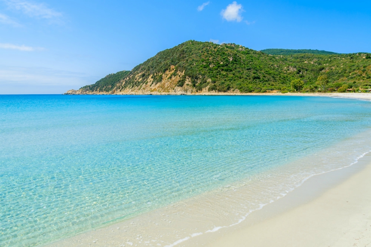 beaches in sardinia | blue water and sand beach under clear skies with green hillside in distance | Cala Pira