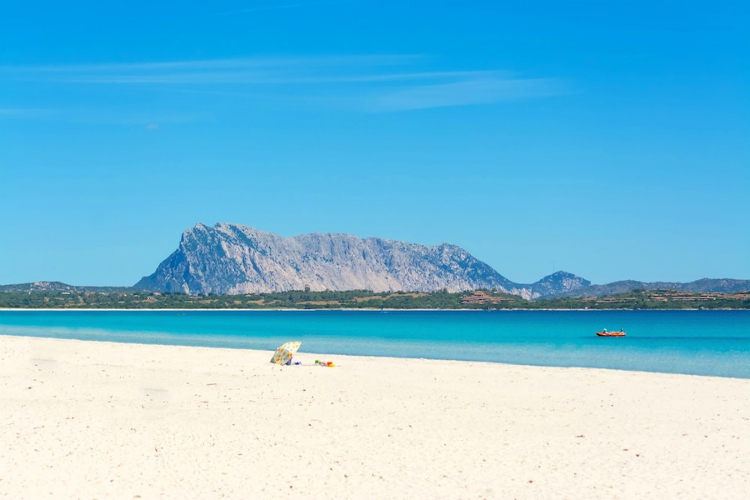 beaches in sardinia | white beach, blue water and mesa in the distance under blue skies | Spiaggia La Cinta