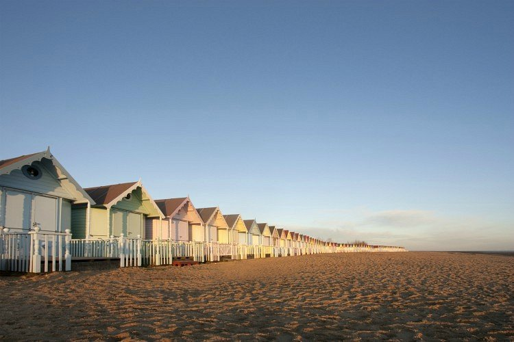 A line of pastel coloured beach huts at mersea in essex, uk