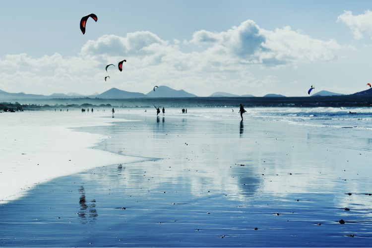 a panoramic view of the Famara Beach in Lanzarote, Canary Islands, Spain, with some unrecognizable swimmers and kitesurfers in the background, in backlit (a panoramic view of the Famara Beach in Lanzarote, Canary Islands, Spain, with some unrecognizab