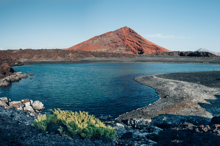 Panoramic view of unique volcanic landscape in Lanzarote island. Black sand, lake and and red mountain. Playa Bermeja. Travel destination. Nature background. unesco heritage. Canary Islands