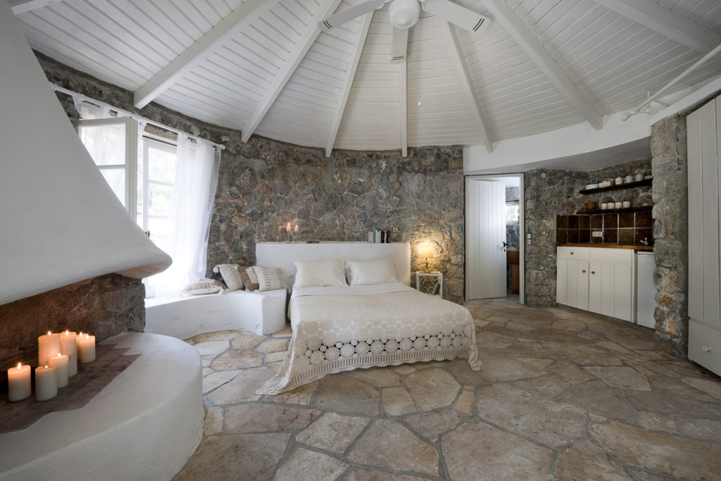 Bedroom within Chapel View in Corfu - rounded room, with feature fireplace and wood-panelled ceiling