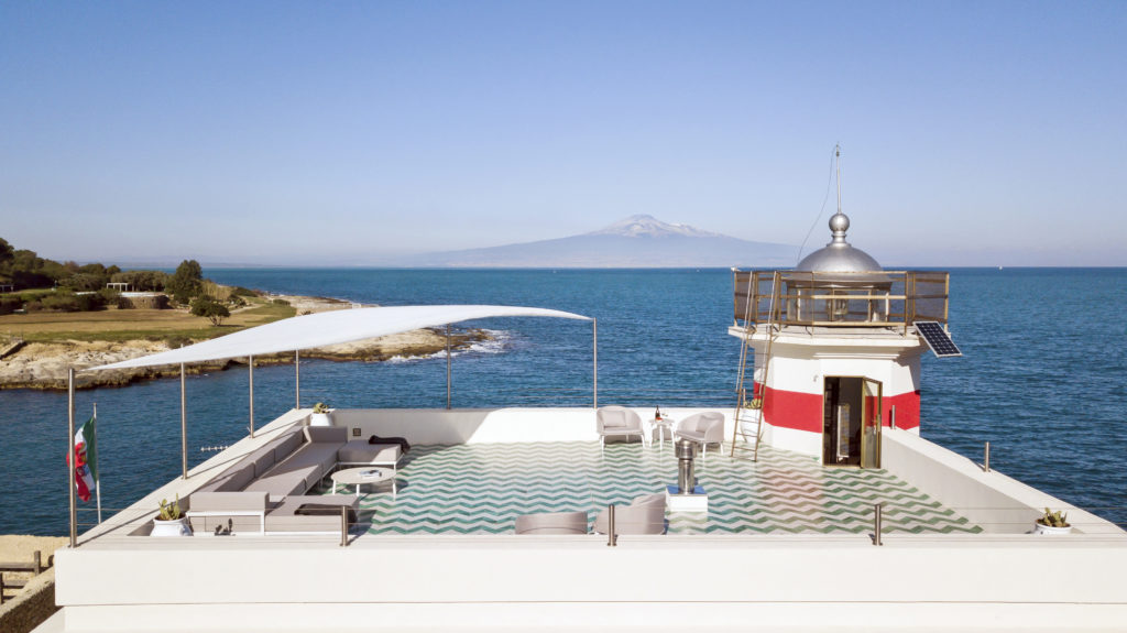 La Lanterna Delle Stelle - converted lighthouse holiday home. Image is of a rooftop terrace looking out over the sea.