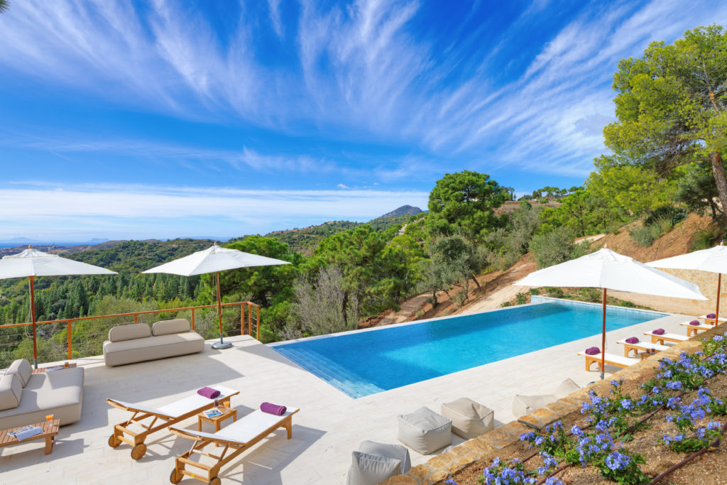 Countryside view from an infinity pool with sun loungers and umbrellas