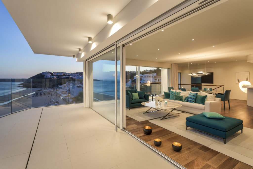 View of living room with night lights and view of beach from balcony