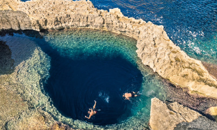 Deep blue hole at the world famous Azure Window in Gozo island - Mediterranean nature wonder in the beautiful Malta - Unrecognizable scuba divers swimming to adventure water cave