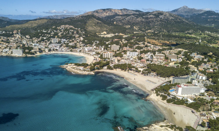 Aerial photograph of the three beaches of Paguera and their skykine, on a sunny summer day.