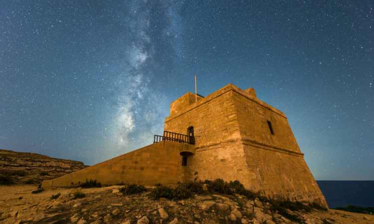 A beautiful Milky Way night time photograph of the Dwejra Watch Tower on the island of Gozo, Malta. With the orange building in the foreground and the stars against a deep blue sky.