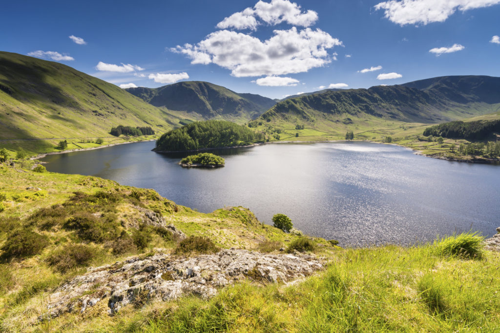 Haweswater Reservoir in Mardale Valley taken from Whiteacre Crag. A green hill that leads down to the water is in the foreground. The water is deep blue and reflects the sunlight. The reservoir is surrounded by rolling green hills, and a deep blue sky filled with fluffy white clouds is overhead