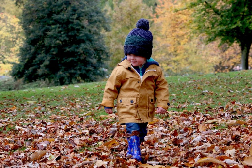 kid playing in leaves with wooly hat on