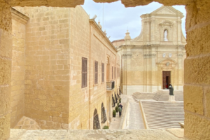 one of the things to do in Gozo: an image of the cathedral through a rocky window