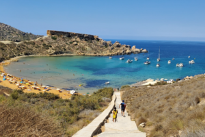 One of the beaches in Gozo, with people walking down stairs to a small bay