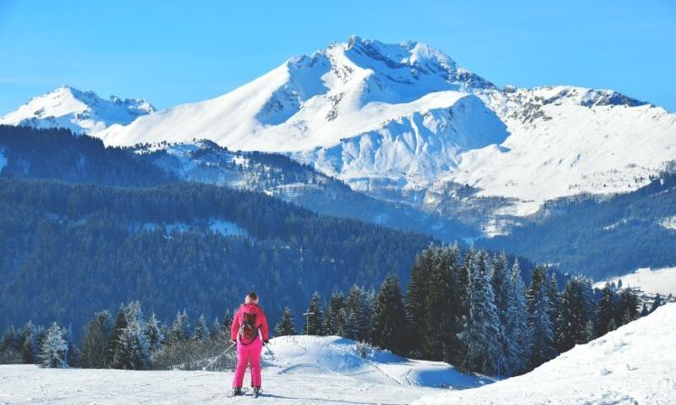 lady in pink ski wear looking out over ski slopes